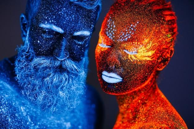 Conceito. retrato de um homem barbudo e uma mulher pintados em pó ultravioleta.