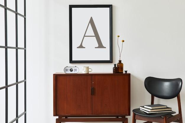 Conceito retro moderno de interior de sala de estar com cômoda de teca de design, moldura preta, relógio, cadeira, decoração, parede branca e acessórios pessoais.