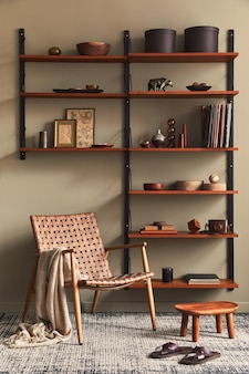 Conceito retro moderno de interior de sala de estar com poltrona elegante, prateleira de madeira, livro, moldura, decoração e acessórios pessoais elegantes na decoração da casa.