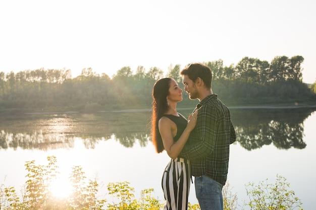Conceito romântico e popular - jovem casal se abraçando perto do rio ou lago e curtindo