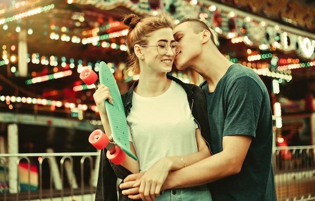 Conceito romântico. lindo, jovem casal apaixonado, se divertindo no parque de diversões.