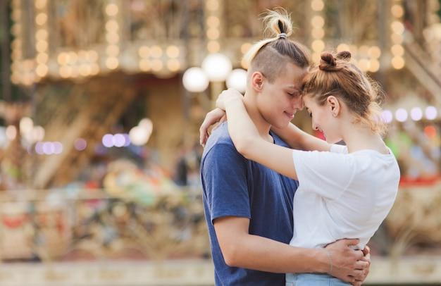 Conceito romântico. lindo, jovem casal apaixonado se divertindo no parque de diversões.