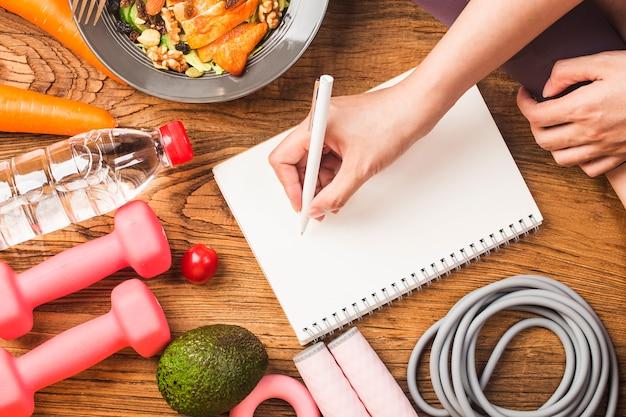 Conceito saudável com alimentação nutricional na lancheira e equipamentos de fitness com mulher escrevendo tempo para ficar saudável no livro de diário