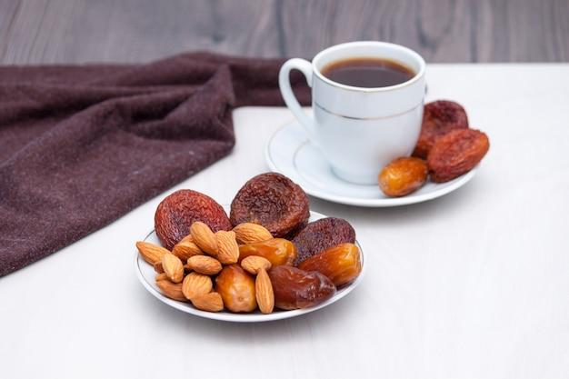 Conceito saudável de café da manhã ou lanche. café preto, frutas secas. copie o espaço.