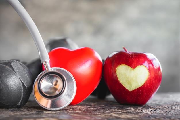 Conceito saudável de lareira com maçã vermelha, halteres e sethocope