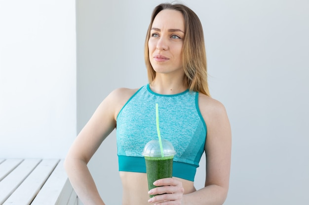Conceito saudável, fitness e desintoxicação - close-up de jovem em roupas esportivas com suco verde dentro de casa