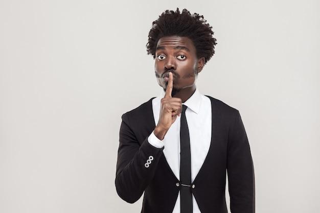 Conceito secreto ou silencioso. empresário africano mostrando sinal de shh para a câmera. foto interna, fundo cinza