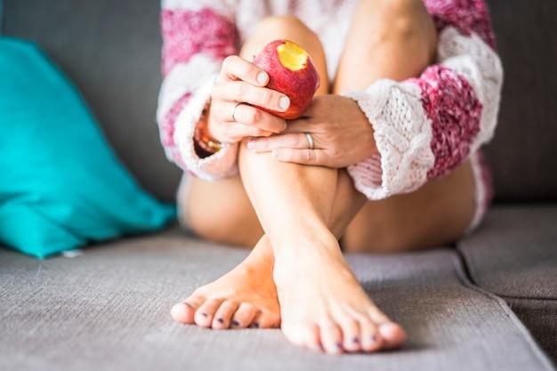 Conceito sexy e saudável para uma garota simpática sentada no sofá comendo uma maçã diet