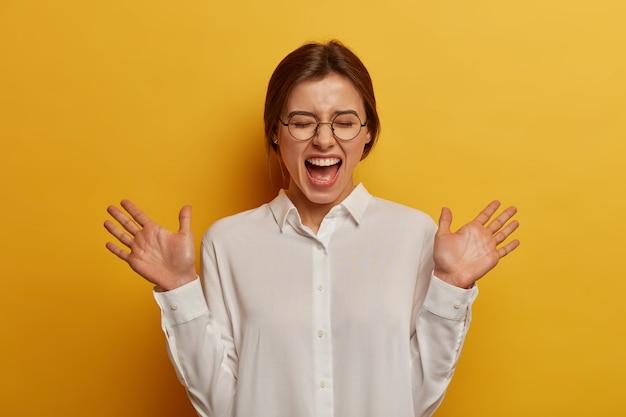 Conceito sincero de emoções e sentimentos. mulher caucasiana exultante levanta as palmas das mãos, ri, fecha os olhos, ouve uma piada engraçada, usa óculos redondos e camisa branca, modelos contra a parede amarela