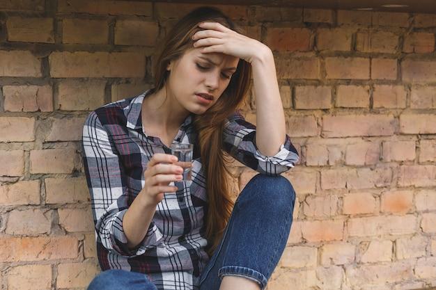 Conceito social alcoólico dos problemas da jovem mulher que senta-se com os olhos fechados na cozinha. depressão jovem adolescente do sexo feminino ter abusado problema sentindo sofrimento e chorando.