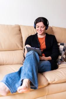 Conceito social da distância no isolamento de quarentena em casa. visão vertical de mulher alegre com fones de ouvido, chamando um amigo doente com dispositivo eletrônico.