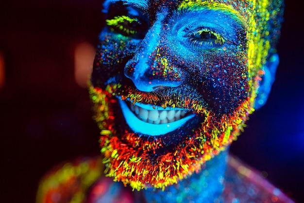Conceito. um homem barbudo sorri. retrato de um homem barbudo pintado em pó fluorescente.