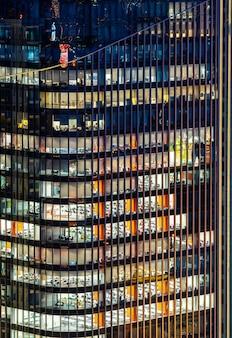 Conceito urbano de trabalho tardio, fachada de janela de arranha-céu de escritório no centro de negócios à noite
