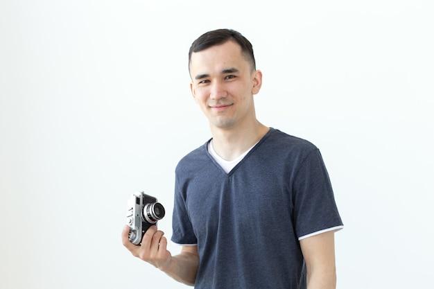 Conceito vintage, fotógrafo e pessoas - bonito homem asiático com câmera retro sobre branco