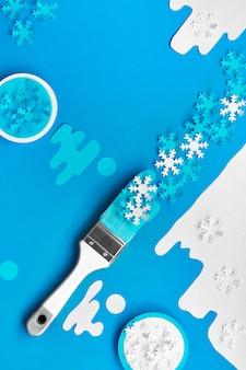 Conceito vista superior plana leigos parede em azul e branco com pincéis carregados com flocos de neve de papel