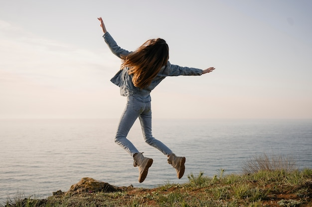 Conceito wanderlust com uma jovem curtindo a natureza ao seu redor