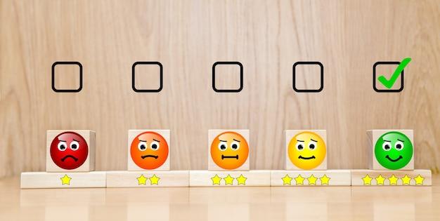 Conceitos de avaliação do atendimento ao cliente e pesquisa de satisfação. a caixa de seleção selecionada sorriso de rosto feliz e símbolo de cinco estrelas no cubo de madeira na mesa