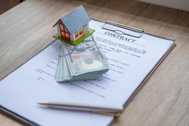 Conceitos de compra da casa, modelo da casa pequena e dinheiro com contrato do original e pena na tabela de madeira.