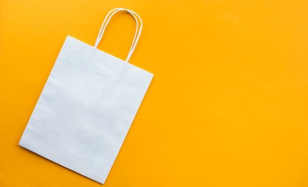 Conceitos de compras com saco branco em papel amarelo