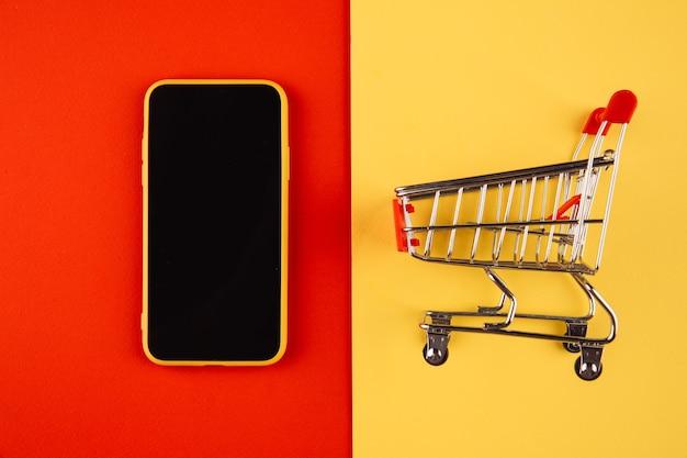 Conceitos de compras online com maquete de carrinho e smartphone em vermelho amarelo.