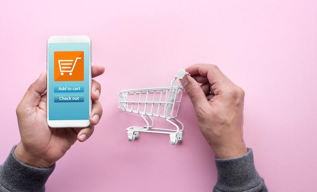 Conceitos de compras online com pessoa e pequeno carrinho e smartphone