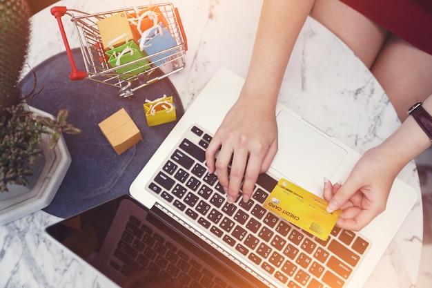 Conceitos de compras online, mãos de mulher usando cartão de crédito e computador portátil