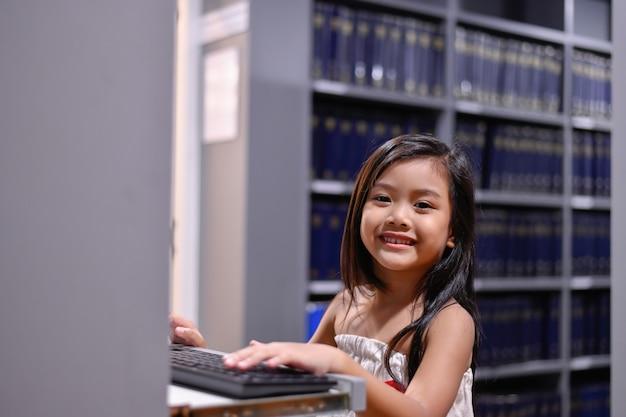 Conceitos de educação. a menina está estudando na biblioteca. lindas garotas são felizes aprendendo.