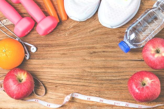 Conceitos de estilos de vida aptos, saudáveis e ativos conceito, garrafa de água, halteres, sapatos esportivos, smartphone com fone de ouvido e maçãs em fundo de madeira. copie espaço para texto. vista do topo