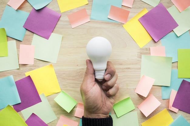 Conceitos de ideias de inspiração com a mão segurando uma lâmpada branca e um papel para cartas