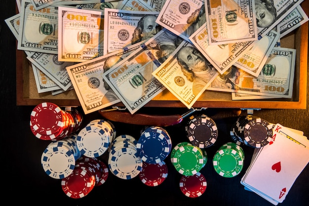 Conceitos de jogos de azar. apostar é uma aposta para os investidores. caixa cheia de fichas, dólares e cartas de jogar em um fundo preto