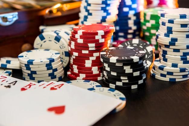 Conceitos de jogos de azar. apostar é uma aposta para os investidores. caixa cheia de fichas, dólares e cartas de jogar em uma parede preta