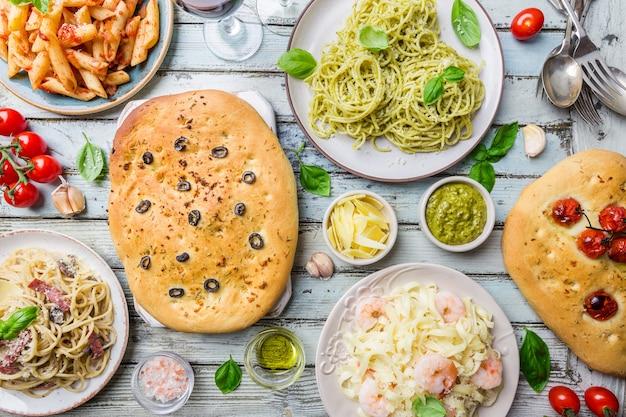 Conceitos de mesa de comida italiana com diversos pratos de massas com diferentes tipos de molhos e pão focaccia