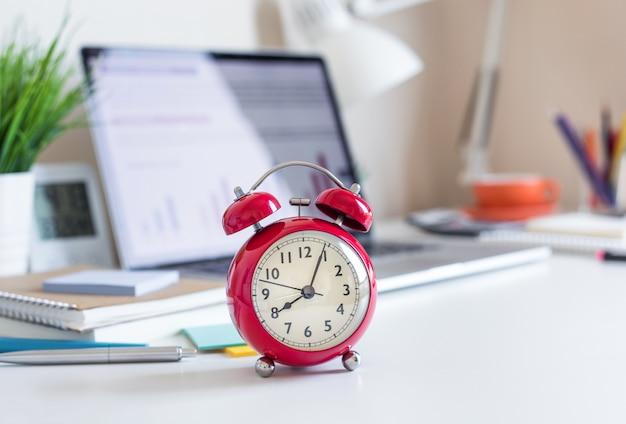 Conceitos de negócios com relógio vermelho na mesa de escritório