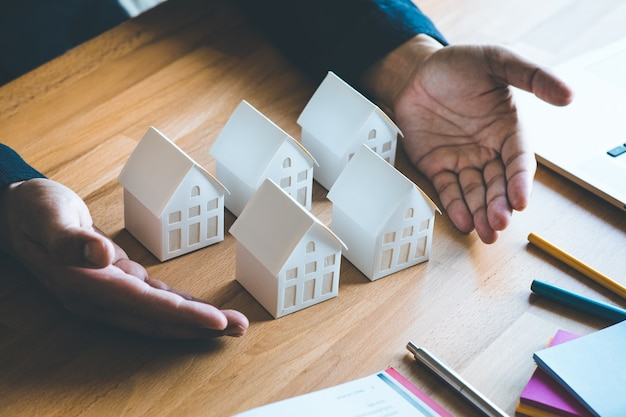 Conceitos de propriedade comercial, imobiliário e de investimento com investidor e casa modelo branca na mesa de trabalho