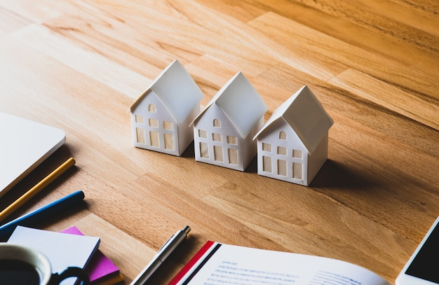 Conceitos de propriedade, imóveis e investimento de negócios com casa modelo branca no fundo da mesa.