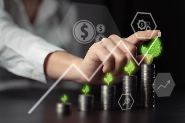Conceitos de tecnologia econômica negócios futuros nova plataforma de negociação ecológica. empresário com pilha de moedas e gráfico de holograma.