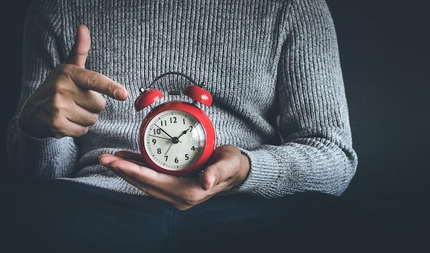 Conceitos de tempo e vida com um homem segurando um despertador no escuro