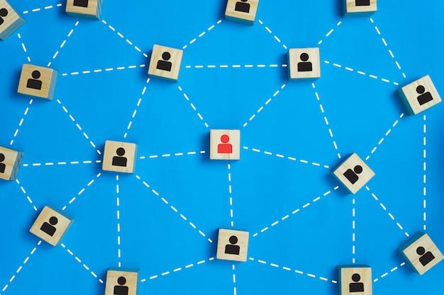 Conceitos de trabalho em equipe de liderança e rede ícone de empresário vermelho em busca do bloco de madeira