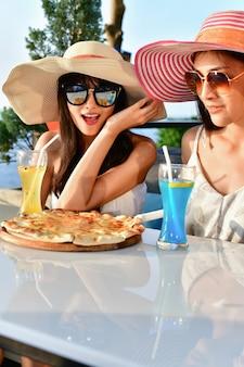 Conceitos de viagem. linda garota está comendo em um restaurante à beira-mar.