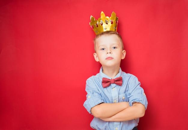 Conceitos felizes de educação e infância com um adorável garoto de 6 anos segurando uma coroa de rei de ouro na cabeça como uma criança mimada e sábia