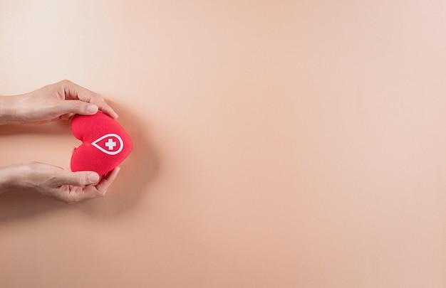 Conceitos médicos e de doadores mão segurando um coração vermelho feito à mão, um sinal ou símbolo da doação de sangue para o dia mundial do doador de sangue
