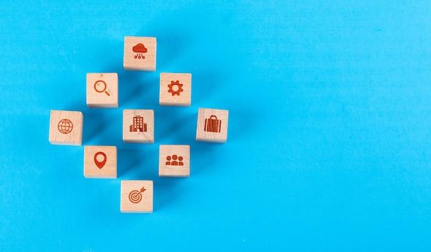 Conceitual de centro médico com blocos de madeira com ícones na mesa plana azul leiga.