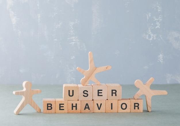 Conceitual de experiência do usuário e negócios. com blocos de madeira com palavras, vista lateral de figuras humanas de madeira.
