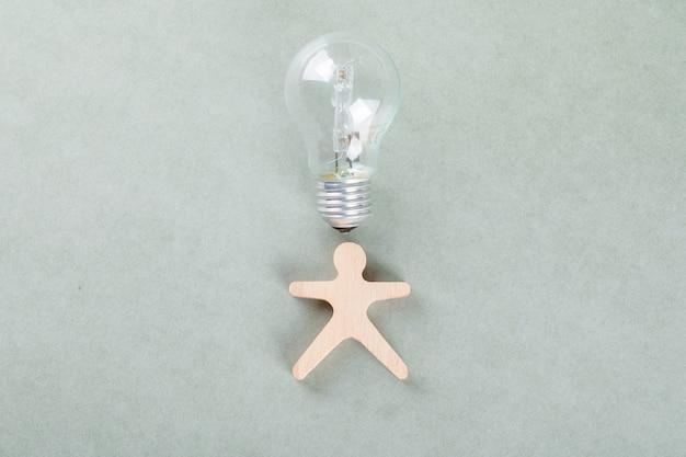 Conceitual de ideia com homem de madeira, lâmpada.