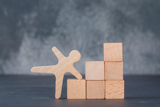 Conceitual de negócios com blocos de madeira como escadas com figura humana de madeira.