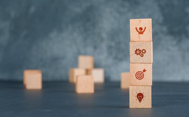Conceitual de negócios com coluna de blocos de madeira com ícones.