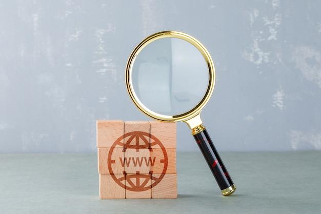 Conceitual de pesquisa na internet com blocos de madeira com o ícone da internet, vista lateral da lupa.