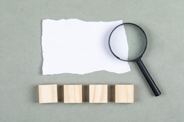 Conceitual de revisitar notas tomadas mão segurando o papel. com papel rasgado na vista superior do plano de fundo cinza. espaço livre para a imagem horizontal do texto