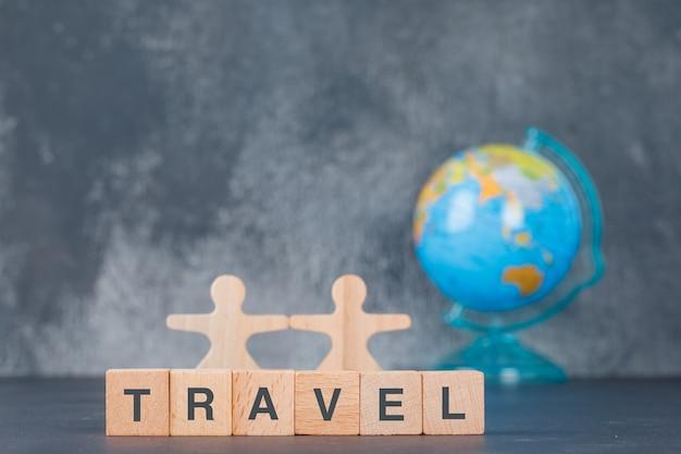 Conceitual de viagem com blocos de madeira com figuras humanas de madeira, globo.