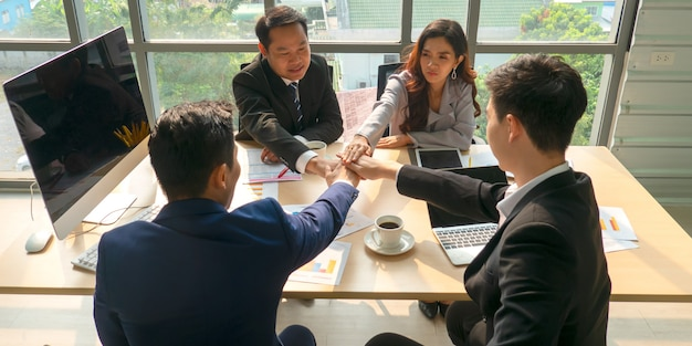 Concentração total no trabalho. grupo de jovens empresários trabalhando e se comunicando enquanto está sentado na mesa do escritório, juntamente com colegas sentados no fundo